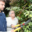 Young man gardening with older woman — Stock Photo