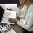 Blond call-center worker sat at her desk - Stock Photo