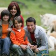 Young family sitting in a field of cattle — Stock Photo