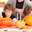 Stock Photo: Children carving halloween pumpkins