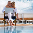 Couple looking at a laptop by a pool — Stock Photo