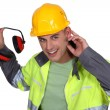 Worker holding hearing protection - Stock Photo