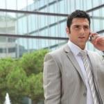 Businessman outdoors talking on phone — Stock Photo