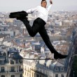 Businessman confidently walking across tight rope - Lizenzfreies Foto