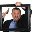Man about to nail a picture frame to a wall — Stock Photo