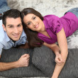Couple laying on cushions on the floor — Stock Photo