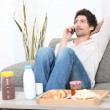 Young man relaxing on the couch and talking on the phone — Stock Photo