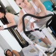 Women using exercise machines in gym - Stock Photo