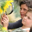Mother and daughter examining a sunflower through a magnifying glass - Stok fotoğraf