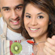 Young man feeding his girlfriend strawberries - Stock Photo