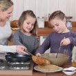 Stock Photo: Mother and daughters making pancakes