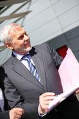 Senior businessman stood outside corporate building — Stock Photo