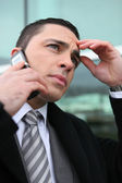 Close-up shot of young businessman on the phone looking preoccupied — Stock Photo