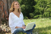 Blond woman sat by tree with laptop deep in thought — Stockfoto