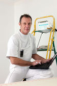Painter perched on ladder whilst using laptop — Stock Photo