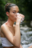 Woman drinking water by a brook — Stock Photo