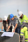 Trabajadores de la construcción en planos del sitio — Foto de Stock