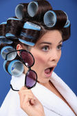 A stunned brunette with hairrollers on. — Stock Photo