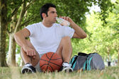Man with a basketball and bottle of water — Stock Photo