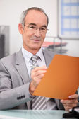 Older man making notes in a file — Stock Photo