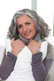 Stylish older woman holding a pillow — Stock Photo