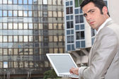 Man using his laptop outside an office block — Stock Photo
