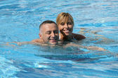 Happy couple swimming together in pool — Stock fotografie