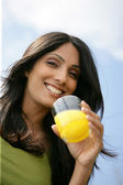 Smiling woman drinking a glass of orange juice — Stock Photo