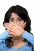 Woman covering her mouth with her hands — Stock Photo