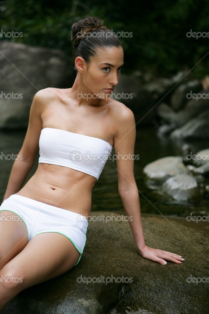Woman sat on large rock in stream — Stock Photo #9233010