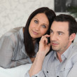 Couple with a phone at home — Stock Photo