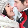 Happy couple kissing in the snow — Stock Photo #9286774