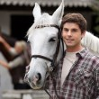 Young man looking after horses - Stock Photo