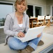 Blond woman sat on patio with latop - Foto de Stock