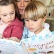 Stock Photo: Mother read book with her two children