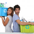 Young couple recycling bottles — Stock Photo