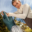 Young woman with a watering can — Stock Photo