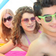 Three young men wearing sunglasses on the beach — Stock Photo