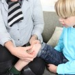 Woman putting bandage to little boy — Stock Photo #9288198