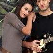 Couple with guitar in front of painted wall — Stock Photo
