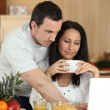 Couple eating breakfast in front of laptop — Stock Photo #9288282
