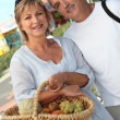 Couple with basket of fruit — Stock Photo
