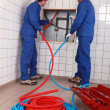 Plumbers installing new hot and cold pipes - Stock Photo