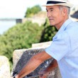 Grey-haired man visiting port town - Stockfoto
