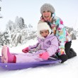 Mother and daughter sledging — Stock Photo