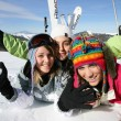 Three female friends laying in the snow — Foto Stock