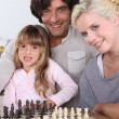 Family playing chess together — Stockfoto
