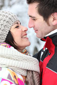 Happy couple kissing in the snow — Stock Photo