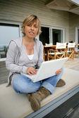 Mujer rubia sentada en el patio con laptop — Foto de Stock