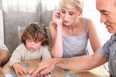 Child building puzzle with mother and grandfather — Stock Photo